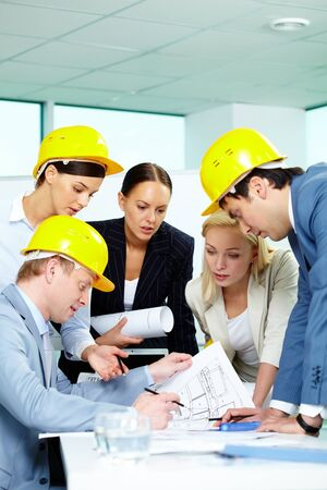 Group of architects looking at a project and discussing it photo