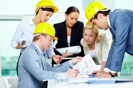 female engineer: Group of architects discussing draft of new construction