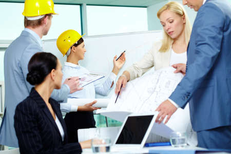 Group of architects interacting in office at meeting photo