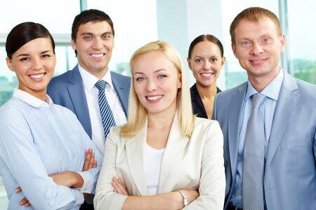 lideres: Retrato del l�der amistoso mirando la c�mara con varios empleados detr�s