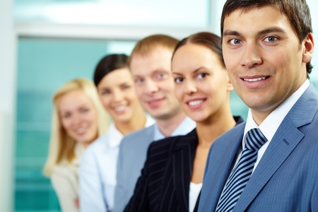 Portrait of friendly leader looking at camera with four employees behind Stock Photo - 9821499
