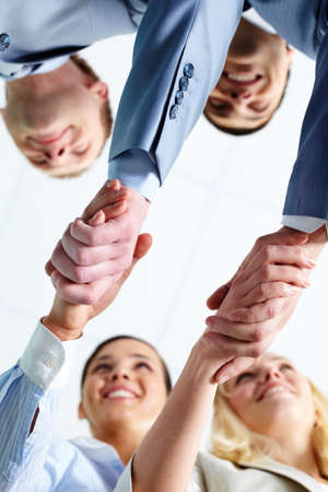Two pairs of successful associates handshaking after striking deal with partners photo