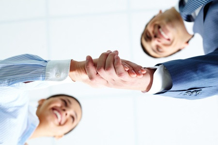 Below angle of successful associates handshaking after striking deal Stock Photo