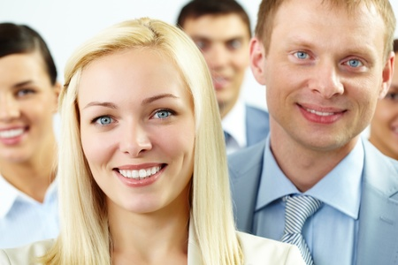 Portrait of cheerful female looking at camera with several employees behind photo