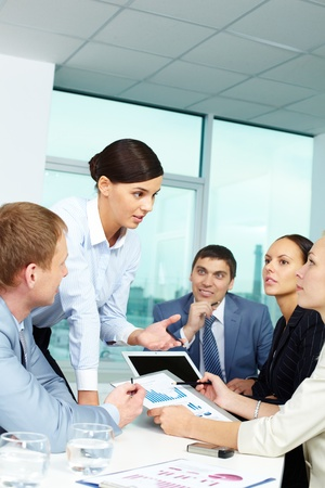 Group of business people discussing papers or sharing ideas in office photo