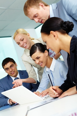 Business team looking at laptop screen while planning work at meeting Stock Photo - 9821541