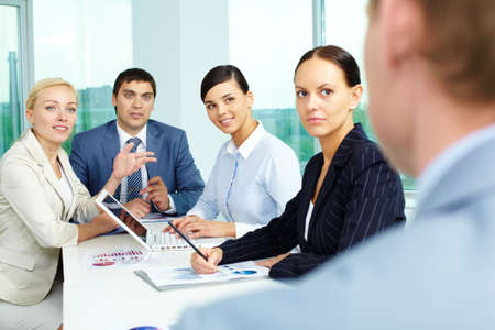 Group of business people looking at their employer while consulting in office photo