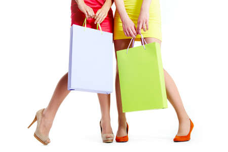 Close-up of beautiful legs of shoppers with paperbags over white background Stock Photo - 9804283