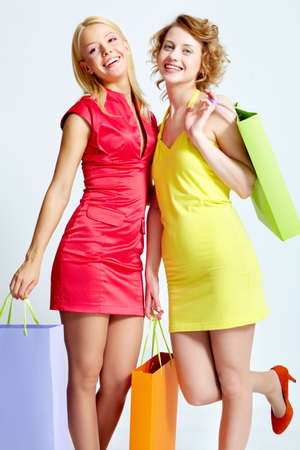 Two beautiful shoppers with paperbags over white background Stock Photo - 9805222