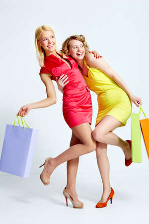 Two beautiful shoppers with paperbags having fun over white background Stock Photo - 9804545