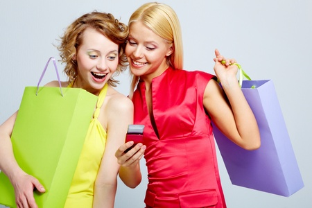Gorgeous shoppers reading sms on mobile phone photo