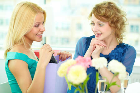 Young girl showing birthday surprise to her friend Stock Photo - 9804550