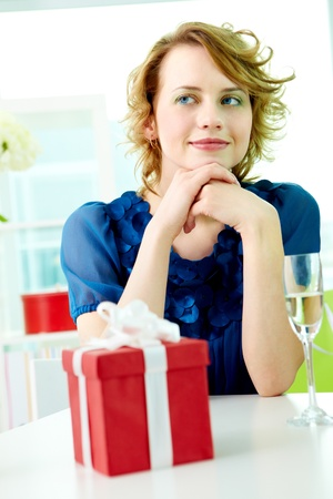 Gorgeous girl sitting at the table with flute and giftbox near by Stock Photo - 9804418