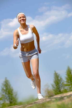Portrait of happy young woman jogging outside photo