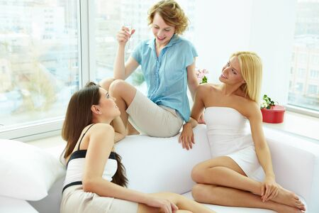 Group of pretty girls relaxing on sofa and chatting at home photo