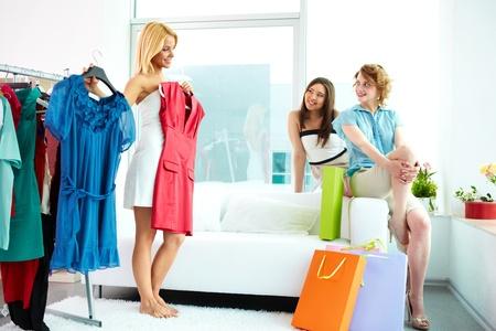 Bild von hübschen Frauen betrachten ihr Freund versucht auf intelligente Kleidung bei der Auswahl eine richtige