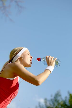 Portrait of a young woman refreshing during workout photo