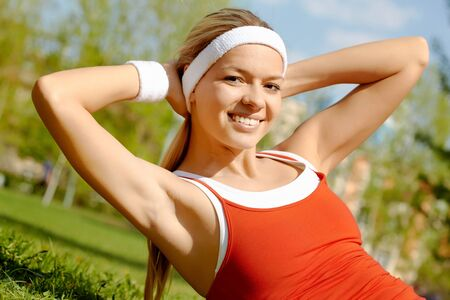 sportswear: Portrait of a young woman doing physical exercise outdoors