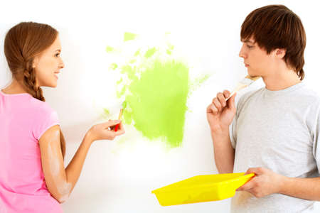 Young happy girl painting wall in new house and looking at pensive guy photo
