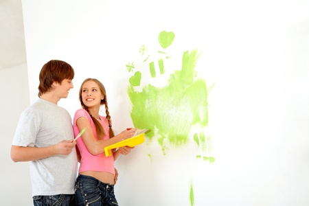 Young happy couple painting walls in new house photo