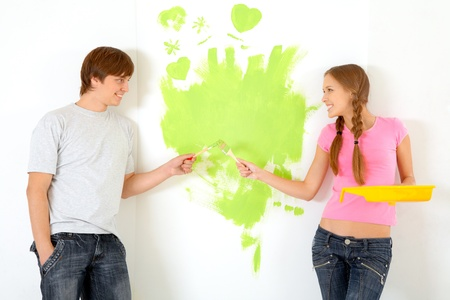 Affectionate couple holding paintbrushes while looking at each other with painted wall on background photo