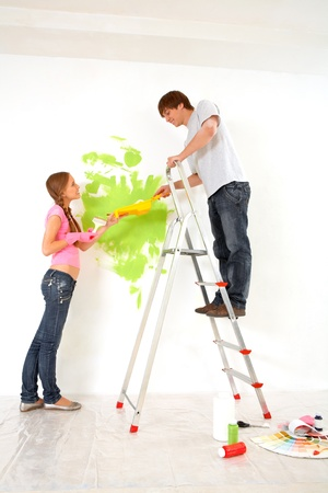Young guy and girl helping each other to paint walls in new house photo