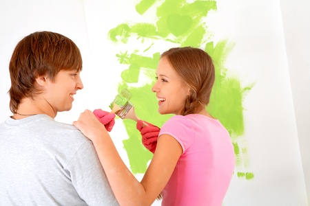 Cheerful couple touching by paintbrushes while looking at each other with painted wall on background photo