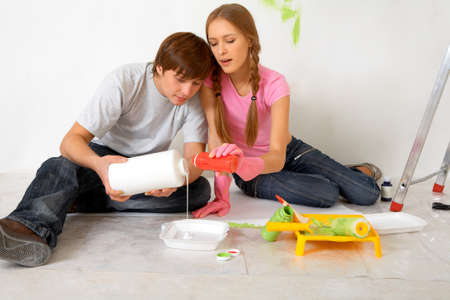 Portrait of creative couple mixing paints while sitting on floor in new flat photo