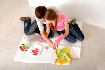 Young couple preparing paints while sitting on floor in new flat photo
