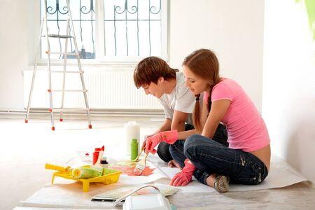 painting wall: Foto de pareja joven mezcla pinta sentado en el piso en piso nuevo Foto de archivo