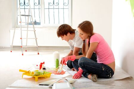 a pair of: Photo of young couple mixing paints while sitting on floor in new flat