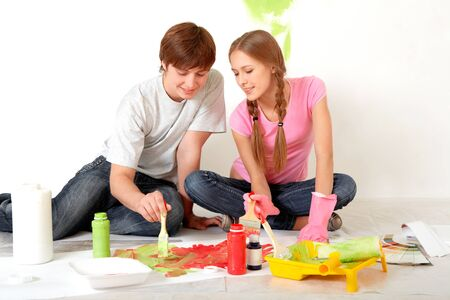 Photo of young couple mixing paints during flat improvement photo