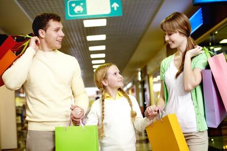 ni�os de compras: Imagen de la familia llevando bolsas e interactuar en el centro comercial Foto de archivo