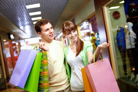 Portrait of smiling husband and wife looking at some goods in the mall Stock Photo - 9821903