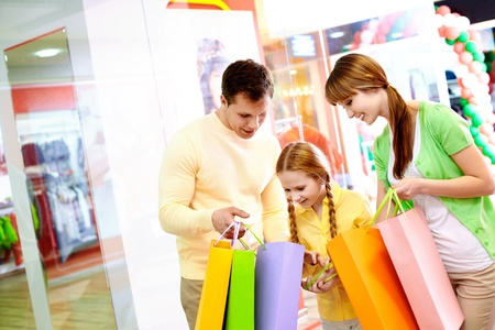 Image of parents showing their daughter what they bought in the mall photo