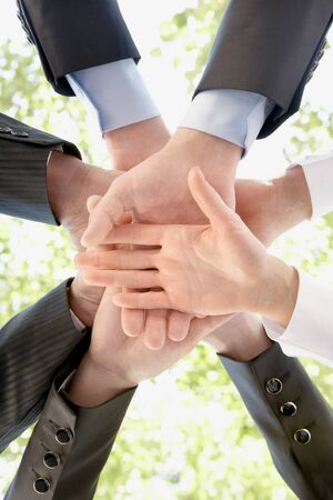 together concept: Bottom view of people hands holding together on background of green foliage