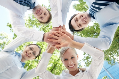 Bottom view of people making pile of hands on background of green foliage Stock Photo - 9821539
