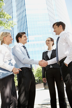 deal: Photo of business partners handshaking at meeting in natural environment