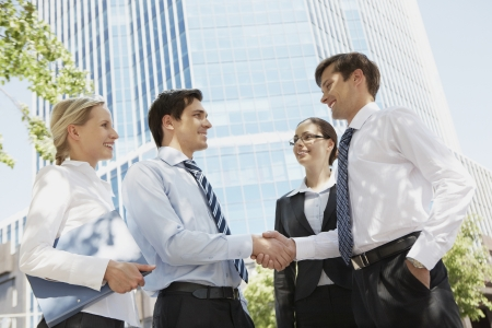 handskakning: Photo of successful associates handshaking after striking deal outdoors at meeting Stockfoto