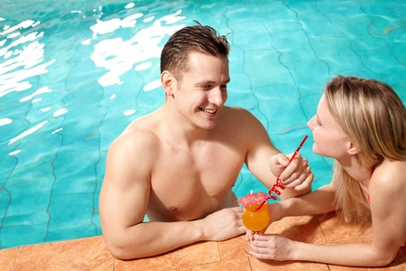 Photo of happy couple in swimming pool chatting with one another  photo