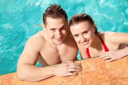 Photo of happy couple smiling at camera in swimming pool Stock Photo - 9805159