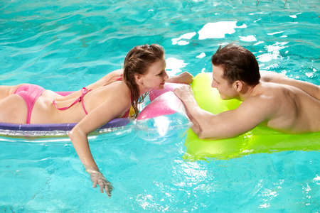 Handsome guy and pretty girl looking at one another in swimming pool photo