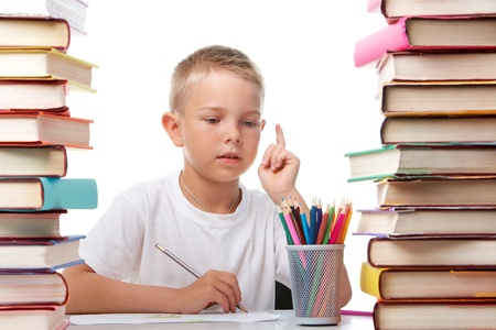 Portrait of cute youngster sitting among stacks of books and thinking while drawing photo