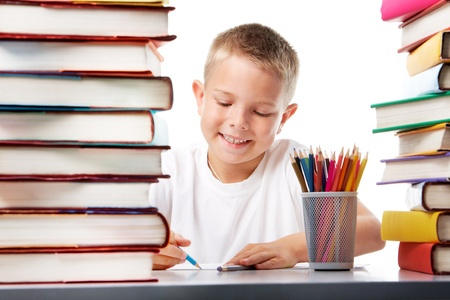 Portrait of cute youngster sitting among stacks of literature and drawing photo