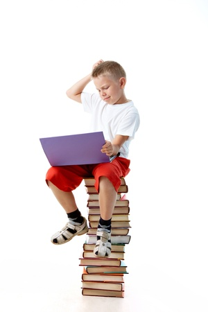 Diligent preschooler sitting on the top of book heap with laptop photo