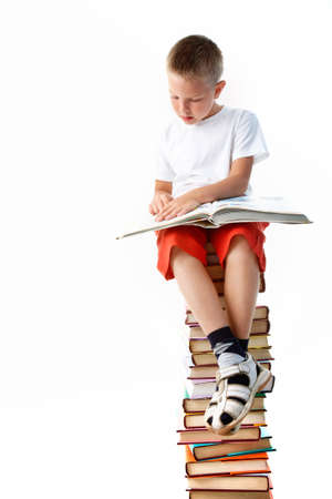 Image of schoolboy sitting on the heap of books and reading one of them photo