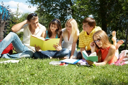Portrait of busy students reading books in park together photo