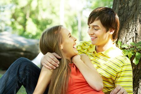 Image of happy couple laughing while having rest outside photo