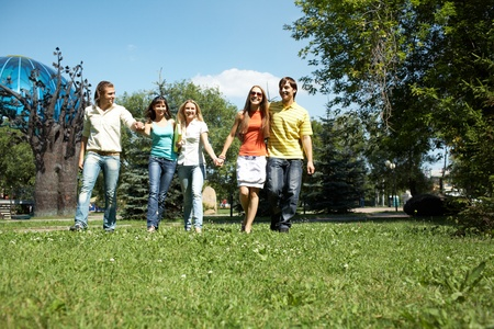 chat group: Photo of cheerful friends walking down green grass in park and chatting