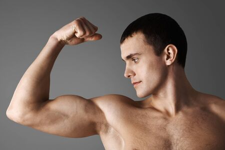 Close-up of strong muscular man over grey background photo